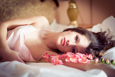 skivvy: closeup portrait of beautiful attractive brunette woman lying in bed with a flower orchid on hand   looking at camera