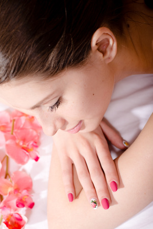 spa treatment: beautiful young attractive brunette woman with flower, pink manicure photo
