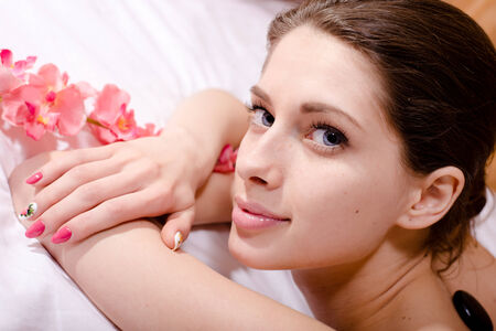 stones with flower: young attractive woman having spa procedures: stones, flower, happy smiling & looking at camera Stock Photo