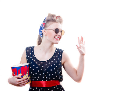 pretty funny young blond pinup woman in polka dot dress with curlers round sun glasses with popcorn happy smiling   waving on white background portrait photo