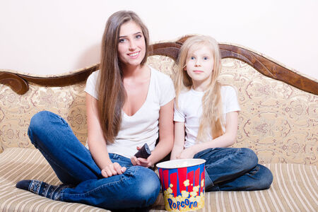 young woman with girl having fun sitting   watching movie, eating popcorn, happy smiling   looking at camera