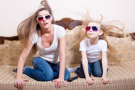 amazed young beautiful woman with blond little girl sitting watching 3D movie in 3D glasses with real life special effects portrait photo