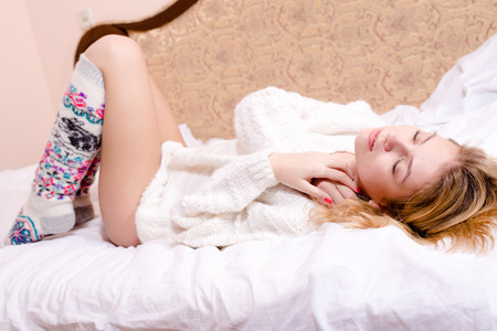 sweet sexy young blond woman lying on her back in white bed in a sweater and socks Stock Photo