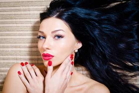 closeup portrait of attractive sexy girl, tempting brunette beautiful young woman with blue eyes, red lipstick   nails looking at camera photo