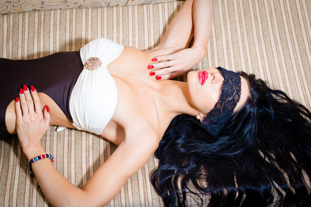 Blindfold beautiful sensual brunette woman with red lipstick, nails and white bra eyes covered in lace ribbon photo
