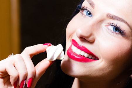closeup portrait on seductive charming beautiful young woman with blue eyes, red lips   hand with red nails holding candy photo