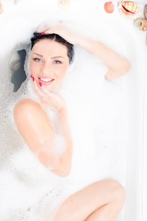 portrait of attractive beautiful sexual blue eyes young woman lying relaxing in the luxury bath with foam happy smiling   looking at camera photo
