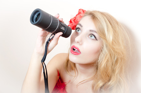 closeup portrait on beautiful glamor young blond pinup woman sexy attractive girl having fun looking peering in spyglass telescope at copy space with red flower in her hair on white background Stock Photo