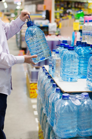 choosing selecting: buyer choosing, selecting or buying a bottle of mineral drinking or distilling water at the shopping store focus on hands on the supermarket display shelf background