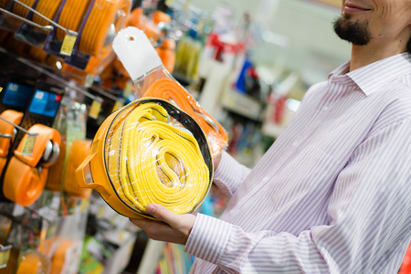 The man with beard buying yellow tow rope at the shopping store closeup on hand on the supermarket display shelf background Stock Photo