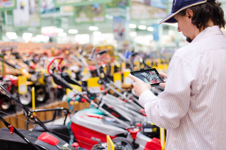 Young man choosing and photographing on the tablet pc computer lawnmowers in garden tools department of DIY shopping store background Stock Photo