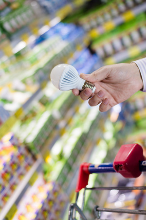 Choosing energy efficient lighting  closeup on male or female hand holding or selecting LED diode light bulb lamp in DIY department store with product display shelfs shop on the background