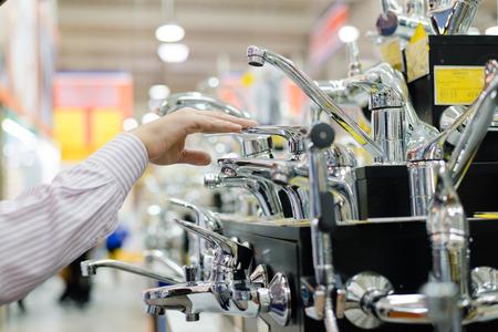 business man or woman choosing and touching faucet crane or water tap on shopping shelf display of DIY department Standard-Bild