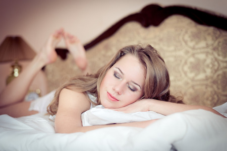 closeup portrait of young beautiful woman having fun relaxing eyes closed lying in pajamas on the white bed photo