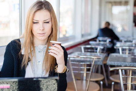 beautiful young blond business woman sitting in a coffee shop drinking coffee and working on laptop computer pc portrait photo