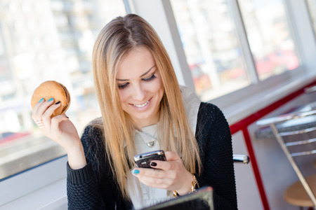 attractive young business woman eating a delicious burger in a cafe or restaurant holding the mobile cell phone chatting and happy smiling closeup portrait photo