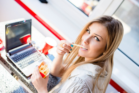 food technology: beautiful blond young business woman sitting at table in restaurant or coffee shop with laptop computer eating delicious fries & looking at camera portrait Stock Photo