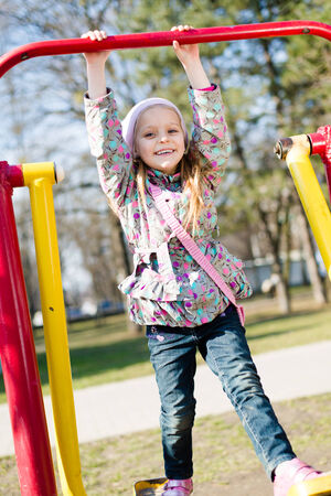 showground: Beautiful funny cute little girl having fun riding a swing looking at camera & happy smiling in the park on spring or autumn outdoors background