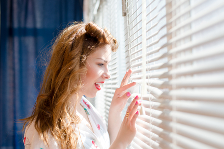 Beautiful young pinup woman looking through white window blinds photo