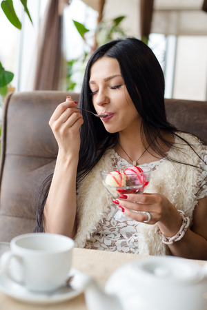 woman with ice cream: image of young happy smiling woman beautiful girl having fun eating ice cream in coffee shop or restaurant closeup portrait