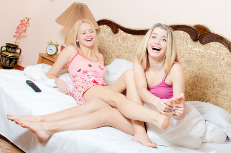 joyful foot massage treatment: beautiful blond girl friends having fun relaxing while younger sister making foot massage older sister on a white bed happy laughing looking at camera Stock Photo