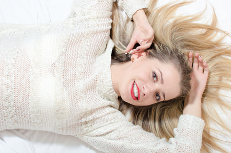 picture of cheerful beautiful blond young woman with green eyes red lips having fun relaxing lying on bed happy laughing and looking at camera closeup portrait photo