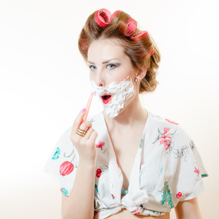 Beautiful young pinup woman shaving face with foam and razor looking in camera isolated on white background closeup portrait photo