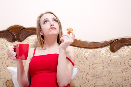 beautiful young woman sitting on white bed in red dress drinking tea and eating cake photo