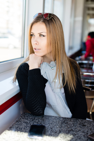 picture of waiting for mobile phone call beautiful cheerful blond young business woman with green eyes relaxing and looking away at copy space image photo