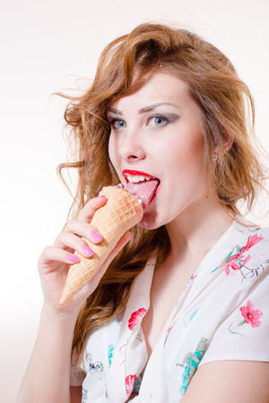 Beautiful young pinup woman eating ice cream cone looking in camera isolated on white background photo