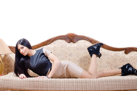 Charming brunette lying on the bed in black  sneakers leather skirt looking at the camera