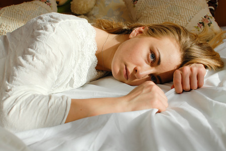 wellness sleepy: picture of emotional beautiful blond young woman relaxing lying in bed looking at copy space on bedroom background closeup portrait Stock Photo