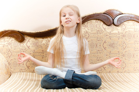 portrait of beautiful school young girl with long blond hair having fun sitting on sofa meditating winking   photo