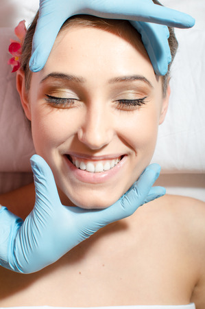enjoyable face massage: close up of beautiful young woman sexy attractive girl with great dental care having fun on spa procedures happy smiling relaxing eyes closed & laying on white bed portrait photo
