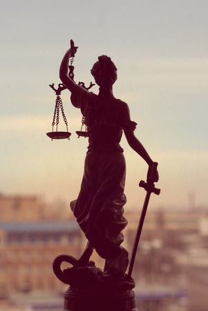 dama de la justicia: la imagen de la diosa Themis o la Señora Justicia de pie en la ventana que sostiene la espada con los ojos vendados en la ciudad al aire libre de antecedentes Foto de archivo