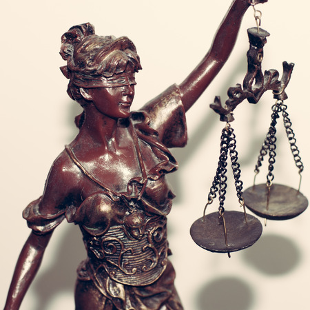 defining: closeup image of Themis goddess or lady justice holding scale blindfold on light background Stock Photo