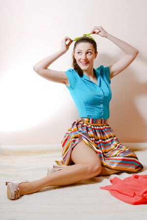 portrait of posing attractive brunette young woman beautiful sexy pinup girl in a striped skirt and blue shirt holding green ribbon having fun happy smiling   looking up at copy space image photo