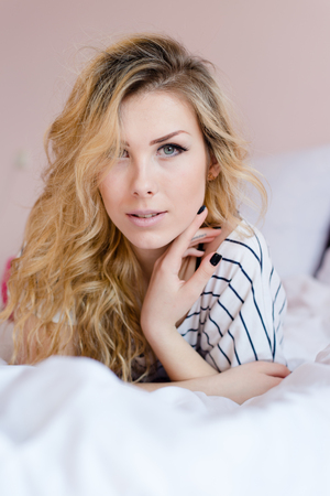 beautiful blond young woman lying in white bed looking at camera photo