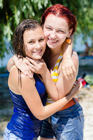 2 girls young women beautiful friends having fun happy smiling wearing wet clothes hugging & looking at camera on summer outdoor background portrait