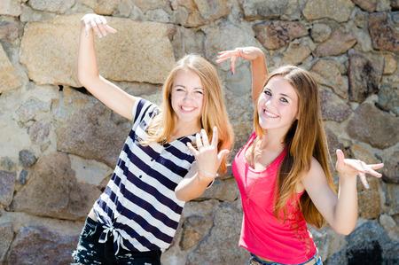 grimacing: 2 funny girls having fun posing grimacing