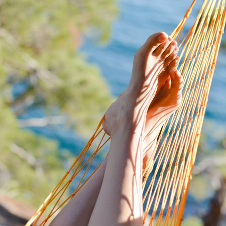 slacker: closeup of feet in a hammock on the beautiful summer sea background Stock Photo