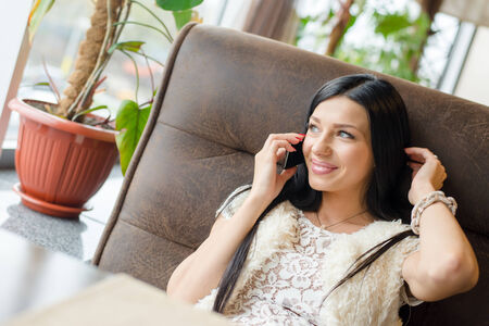 beautiful brunette woman sexy girl having fun sitting in a restaurant lounge or coffee shop and talking on mobile cell phone, happy smiling touching her hair photo