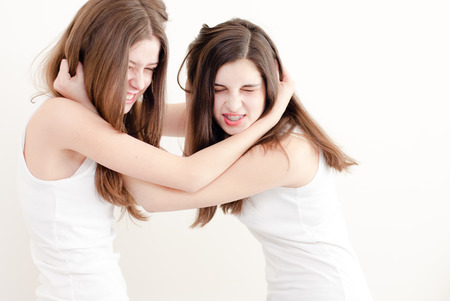 2 funny girls young women in white shirts having fun smiling fighting with each other photo