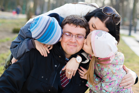 Happy family of 4 celebrating closeup portrait: Parents with two children having fun hugging & kissing father who is happy smile & looking at camera on spring or autumn day outdoors background photo