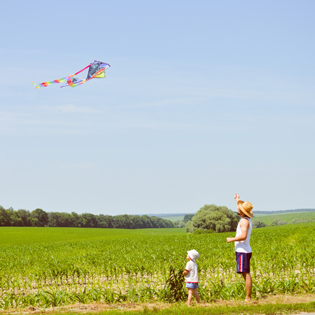 happy family moments: image of father & son having fun playing with kite outdoors on summer sunny day, green field & blue sky outdoors copy space background photo