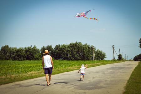 happy times: image of father & son having fun playing with kite outdoors on summer sunny day green woods & blue sky outdoors copy space background photo
