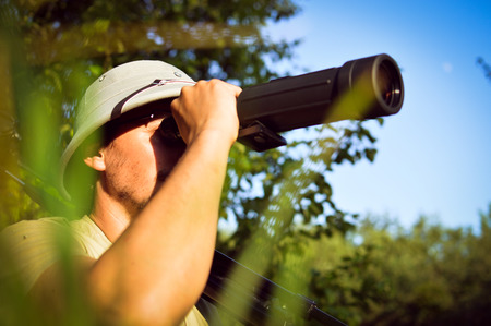 bird watcher: exploring scientist observing romantic male in pith helmet having fun looking in magnification scope on summer sunny day green woods & blue sky outdoors copy space background portrait picture