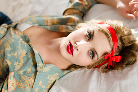 young beautiful blond woman sexy pinup girl in floral shirt having fun relaxing lying on back in white bed & looking at camera closeup portrait picture photo
