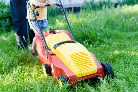 every little help counts: image of grass trimming or lawn mover machine operating or pushing by small boy or girl with adult behind on green copy space background photo