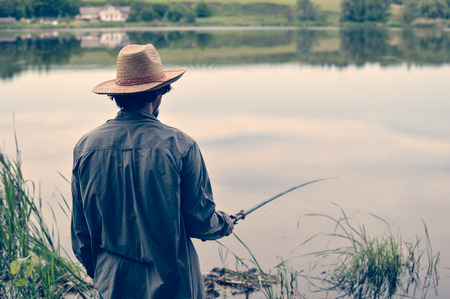 picture of man in straw hat having good time & fun fishing on river bank on peaceful summer day & water outdoors copy space background portrait photo